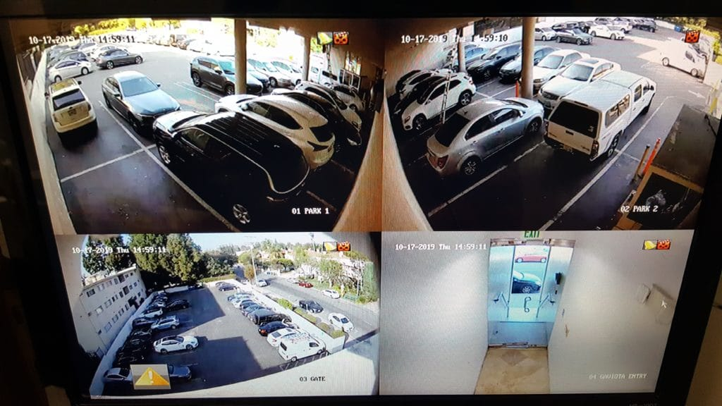 monitor showing footage from 4 different security cameras