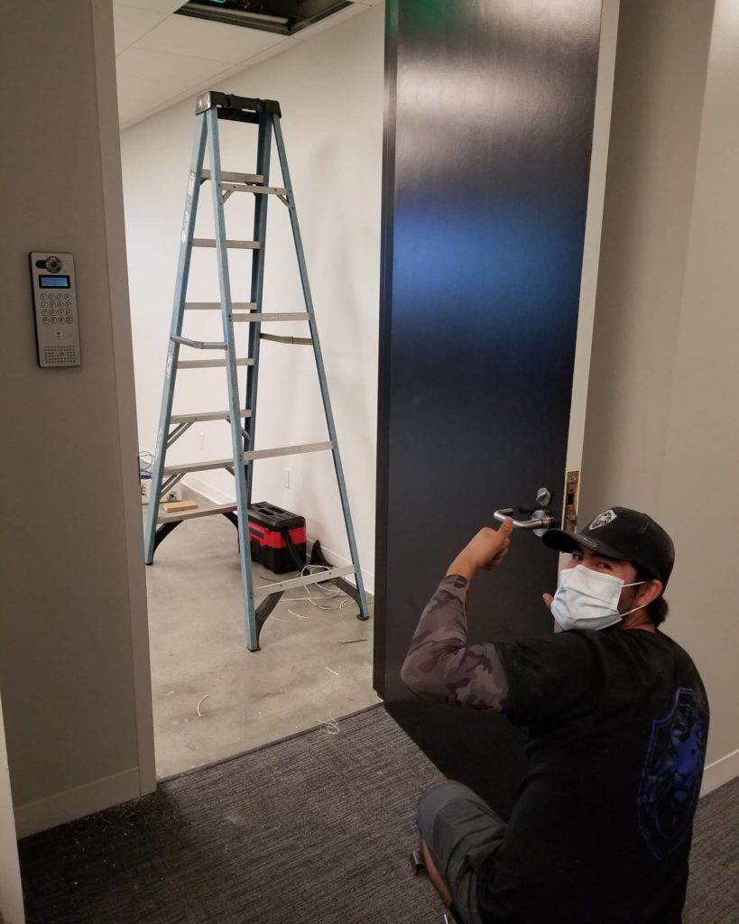 Image of Marco installing an electronic access control panel in a office building